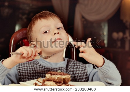 Contented little boy eating a large slice of creamy cake for dessert as he sits smiling with pleasure at the dining table - stock photo