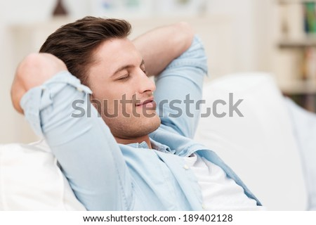 Contented man relaxing at home leaning back on the sofa with his hands clasped behind his head and a smile of pleasure on his face - stock photo