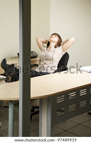 Contented woman in office sitting in chair looking up