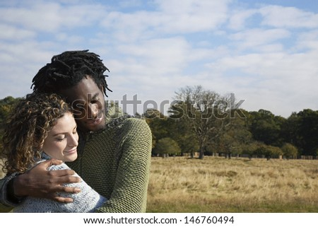 Contented young multiethnic couple embracing in field - stock photo