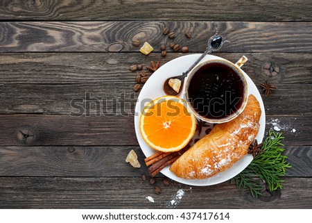Continental breakfast - cup of hot coffee, croissant and orange. Tasty food on rustic wooden background. Top view, place for text. - stock photo