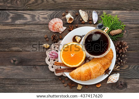 Continental breakfast - cup of hot coffee, croissant and orange. Tasty food on rustic wooden background with sea shells. Top view, place for text. - stock photo