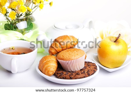 continental breakfast with croissants, cake, chocolate cookies, apple and tea