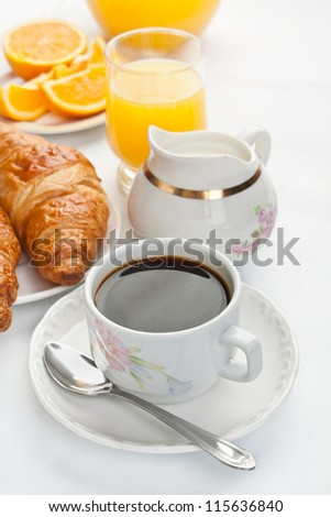 Continental breakfast with fresh coffee, croissants, fruits and orange juice on white background