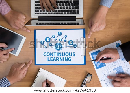 CONTINUOUS LEARNING Business team hands at work with financial reports and a laptop, top view - stock photo