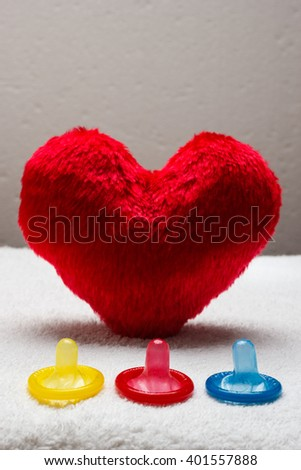 contraception love and birth control. Colorful condoms and red heart shaped little pillow - stock photo
