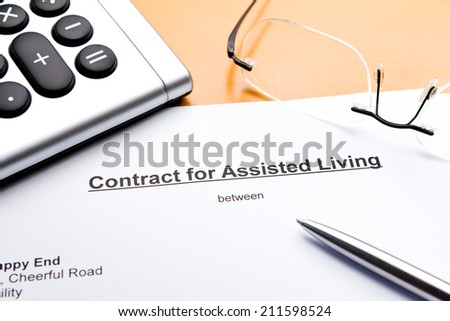 Contract for Assisted Living with calculator, glasses and ballpoint pen - stock photo