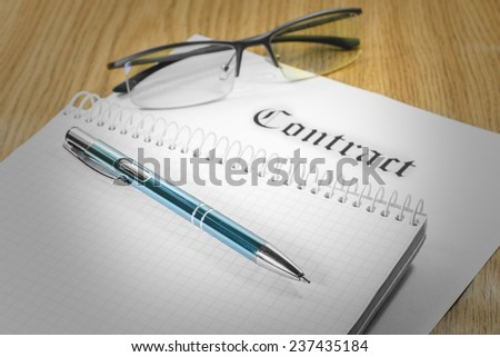 Contract glasses notebook pen on the table