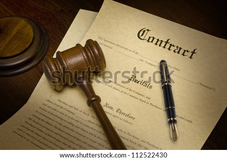 Contract on a wooden desk with a gavel and fountain pen - stock photo