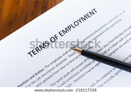 Contract outlining the terms of employment with a pen - stock photo