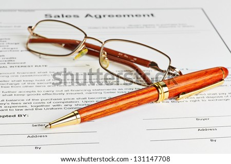 Contract with glasses and wooden pen ready to be signed. Selective focus - stock photo