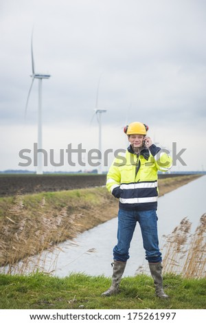Contractor communicating in the field and calling his clients while he is standing in the grass with windmills in the background