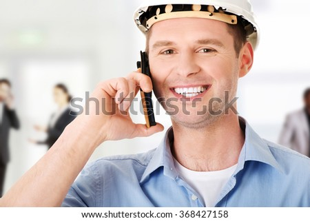 Contractor in hardhat talks on his cell phone. - stock photo