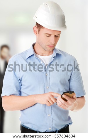 Contractor in hardhat using his cell phone. - stock photo