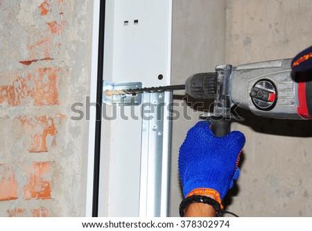 Contractor Installing Garage Door. Repairman use automatic screwdriver to drill the wall for garage door installation. - stock photo