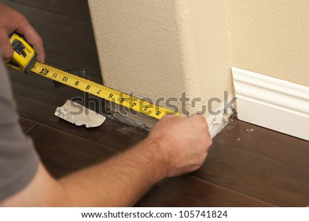 Contractor Measuring for New Baseboard with Bull Nose Corners and New Laminate Flooring Abstract. - stock photo