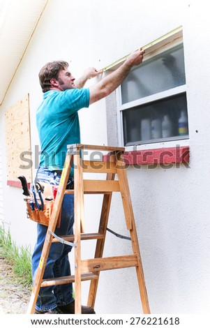 Contractor measuring window to cover with hurrican shutters.   - stock photo
