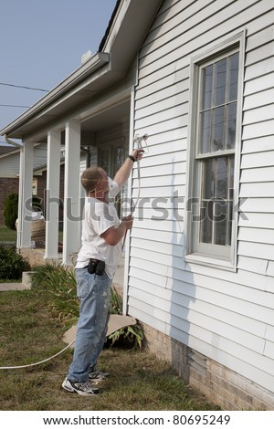 Contractor spray painting exterior of house, getting it ready for resale