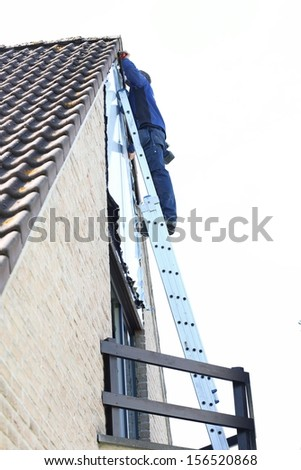 Contractor worker stands on the extension ladder performing task to repair the side of the house under the roof - stock photo