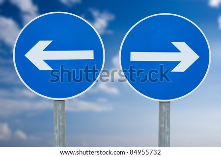 Contradicting directional signs against blue sky - stock photo