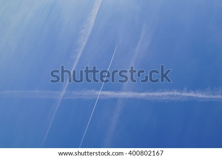 contrails in the blue sky - natural background, texture