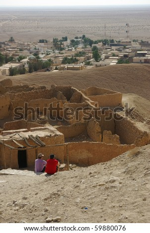 contrast between an old tunisian town in ruins and a modern town - stock photo