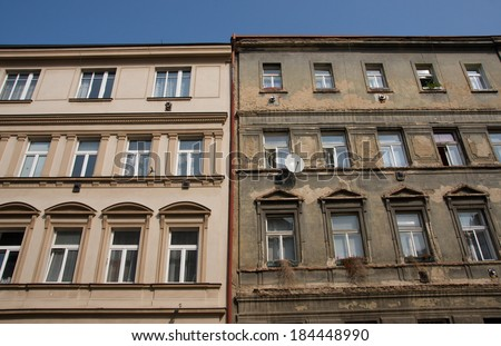 Contrast between old buildings one plaster is repaired and looks good and second is in bad condition. - stock photo