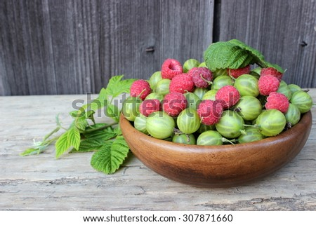 Contrast composition with red raspberry and green gooseberry - stock photo