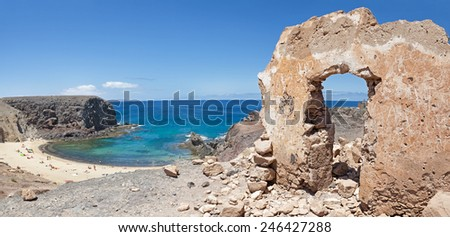 Contrast of the ruins of an old building in front and beautiful Playa de Papagayo in the background; on Lanzarote, Canary islands, Spain. - stock photo