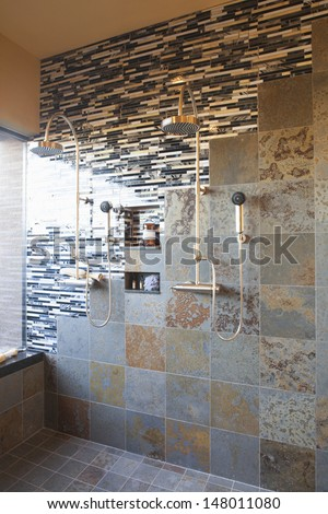 Contrasting tiles in wet room with double shower head - stock photo