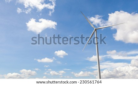 Contrasting white wind turbine and beautiful cloudy blue sky background, in wind farm Thailand for producing renewable electric energy.