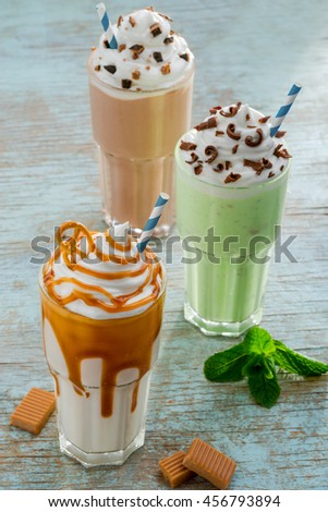 Contrastive shot of different colors and ingredients of milkshakes. Traditional drink in America with ice cream, milk, mint, kiwi, caramel, vanilla and chocolate. Served shakes with blue straws. - stock photo