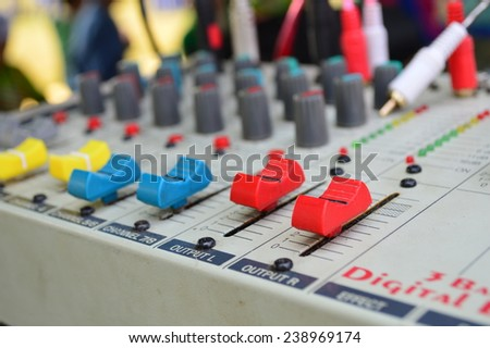 Control buttons for electronic sound. A sliders of a mixing console. Audio signals modifications to achieve the desired output. Applied in recording studios, broadcasting, TV and film production