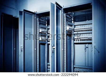 Control panel with circuit-breakers and tangled cable leads - stock photo