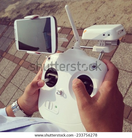 Controlling a remote helicopter drone with smartphone preview - instagram filter - stock photo