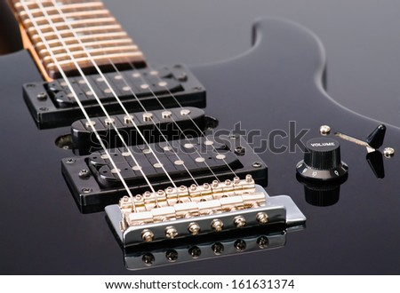 controls and cords, of a black electric guitar - stock photo