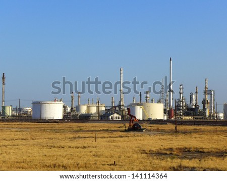 Conventional energy, as referenced by a foreground oil well pumping unit and a refinery in the background - stock photo