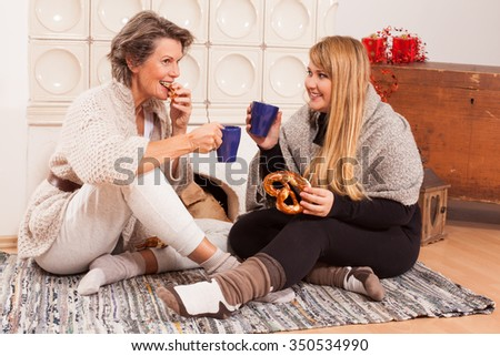 Conversation between two women of different generations with a cup of hot drink and pastries sitting on the floor in front of a warming fireplace. - stock photo