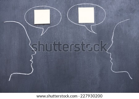 Conversation. Blackboard drawing of two people imitating conversation  - stock photo