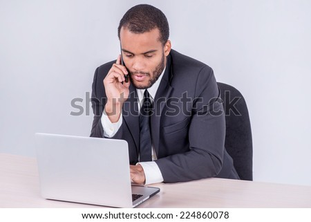 Conversation with the client. Smiling African businessman sitting at desk talking on a cell phone while businessman sitting at the table and working on a laptop isolated on a gray background - stock photo