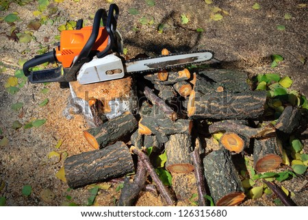 converted timber and petrol-powered saw on the ground - stock photo