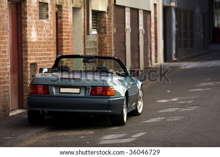 Convertible Sports car on a road with lots of buildings in the background. - stock photo