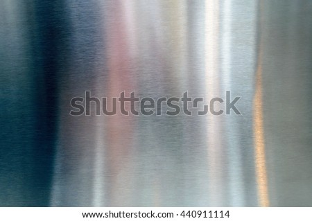 Convex polished shiny steel metal surface with multicolored reflections and glare - stock photo