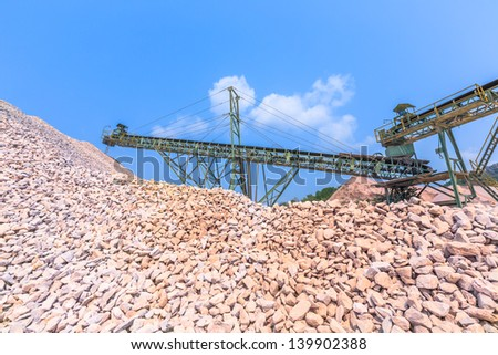 Conveyor and pile of quarry stone for lime industry against white cloud and blue sky - stock photo