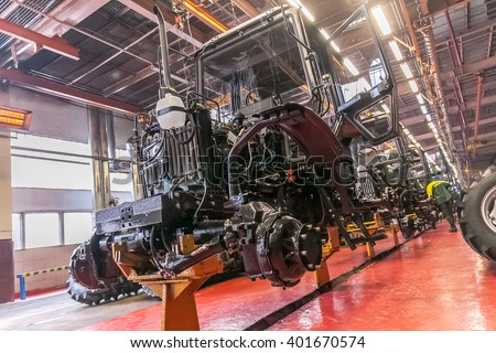 conveyor assembly stage  the body of tractor at factory - stock photo
