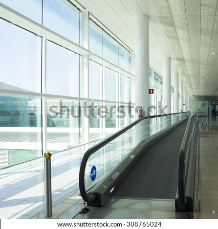 Conveyor belt for people, in a luminous terminal of an airport - stock photo