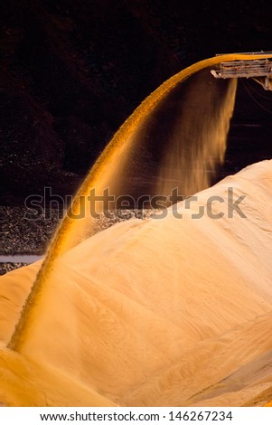 Conveyor belt in a lignite quarry transporting sand during sunset - stock photo