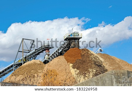 Conveyor Dumping Wood Chips and Biomass in a Pile at a Paper Mill - stock photo
