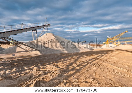 Conveyor of a gravel pit in the evening in front of cloudy sky