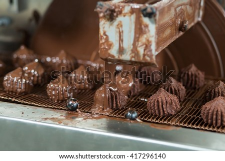 Conveyor pouring liquid onto sweets. Dark candies on conveyor line. Dessert produced at local plant. Chocolate glaze for tasty candies. - stock photo